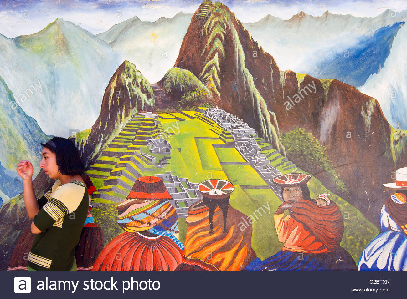 A woman standing in front of a mural painting of Machu Picchu. - Stock Image