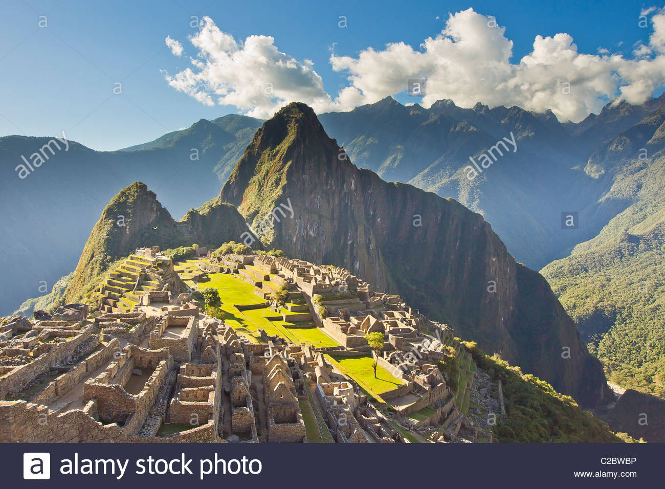 Sun shining through the Andes mountains onto Machu Picchu at sunset. - Stock Image
