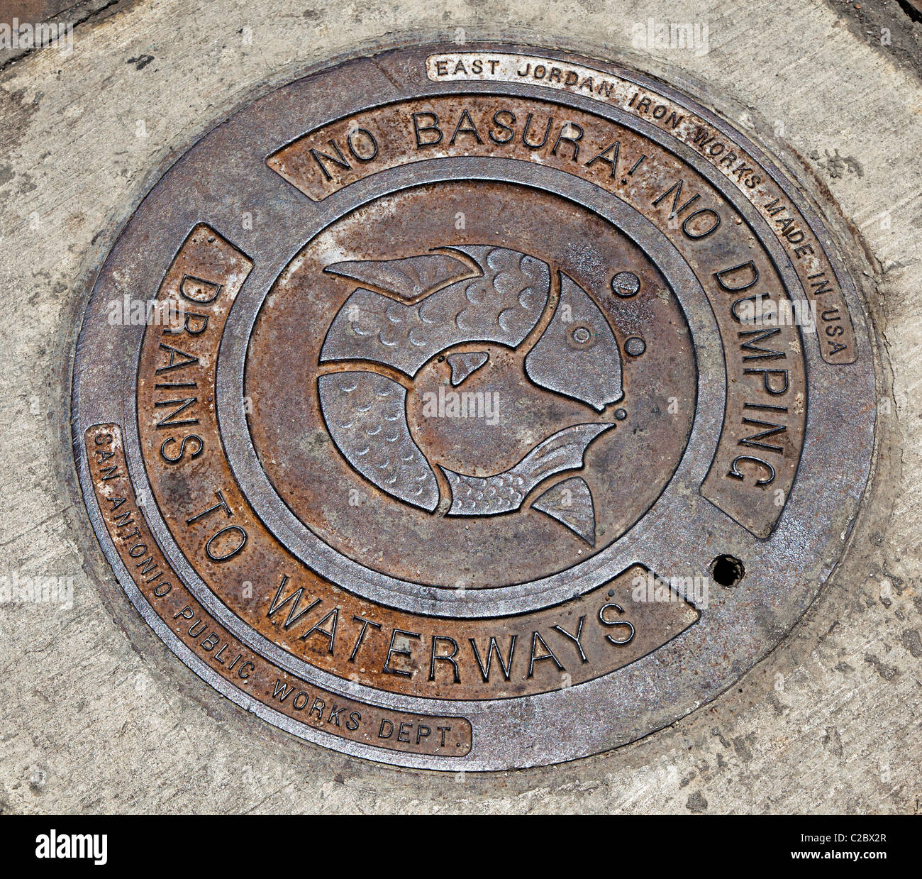 Manhole cover marked with warning no dumping into water and a symbol of a fish San Antonio Texas USA - Stock Image