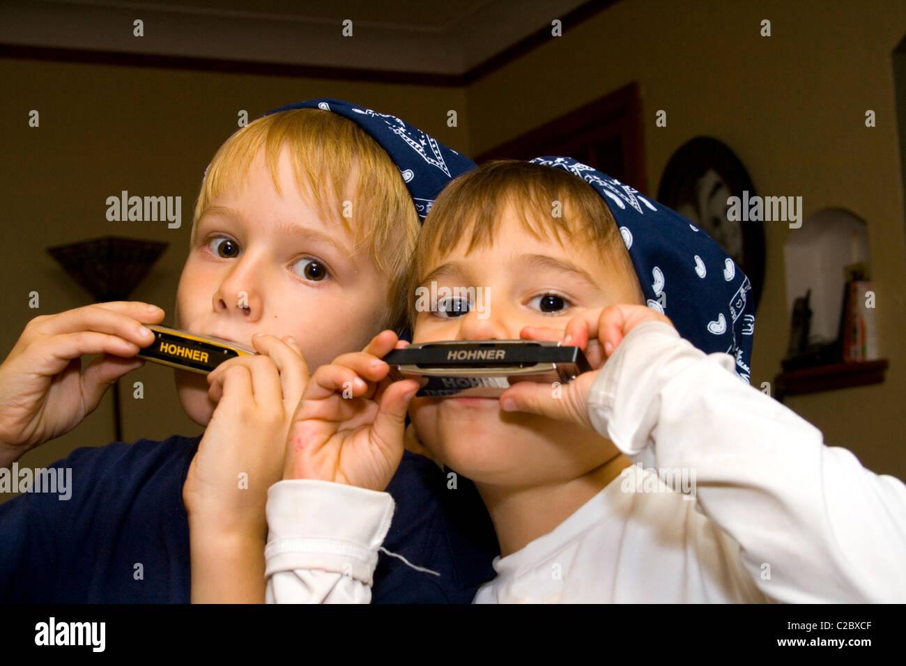 Brothers age 5 and 8 wearing bandanas and playing harmonicas.  St Paul Minnesota MN USA - Stock Image