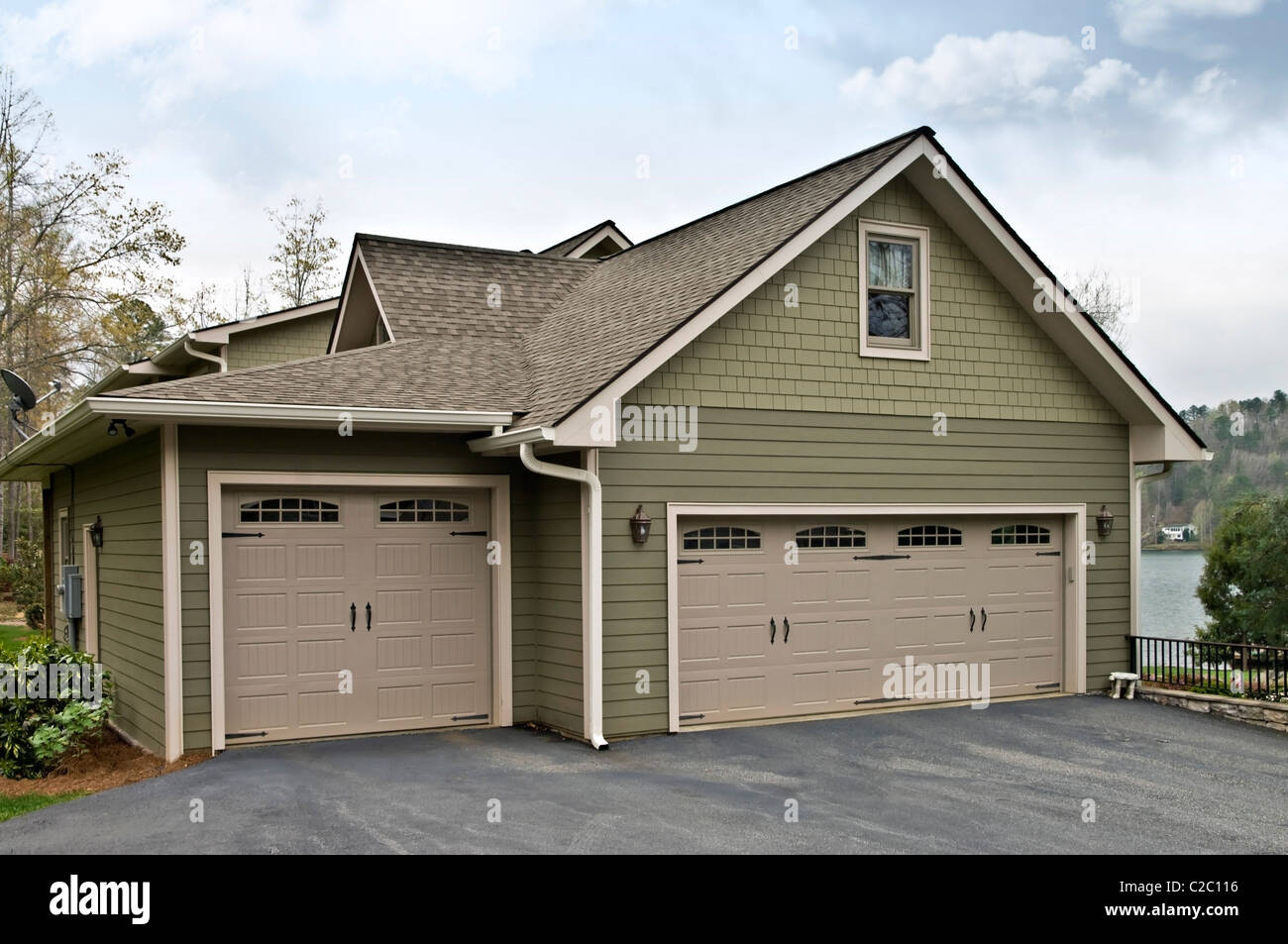 Side of a modern home showing the three garage doors. - Stock Image