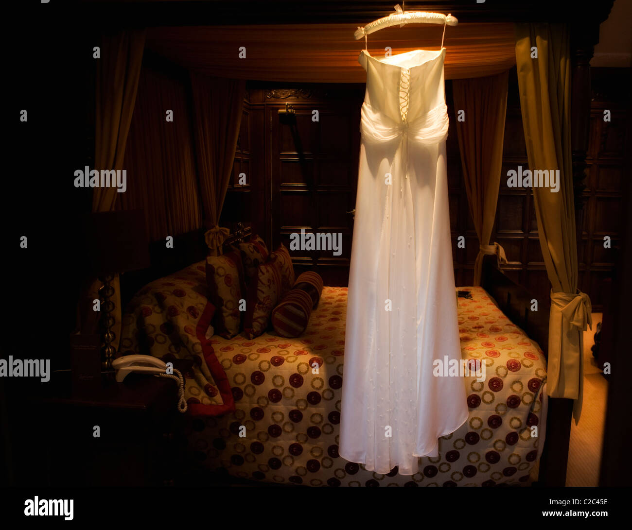 Wedding Dress on 4 poster bed - Stock Image