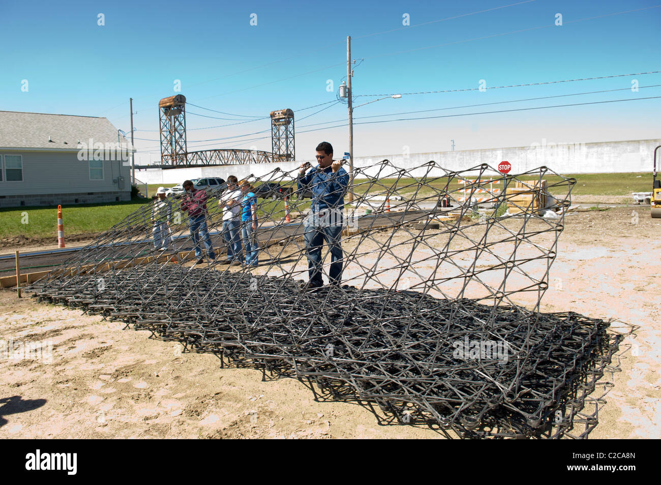 Molten lava rebar being used as reinforcement during first public street pervious concrete pour in 9th Ward, New - Stock Image