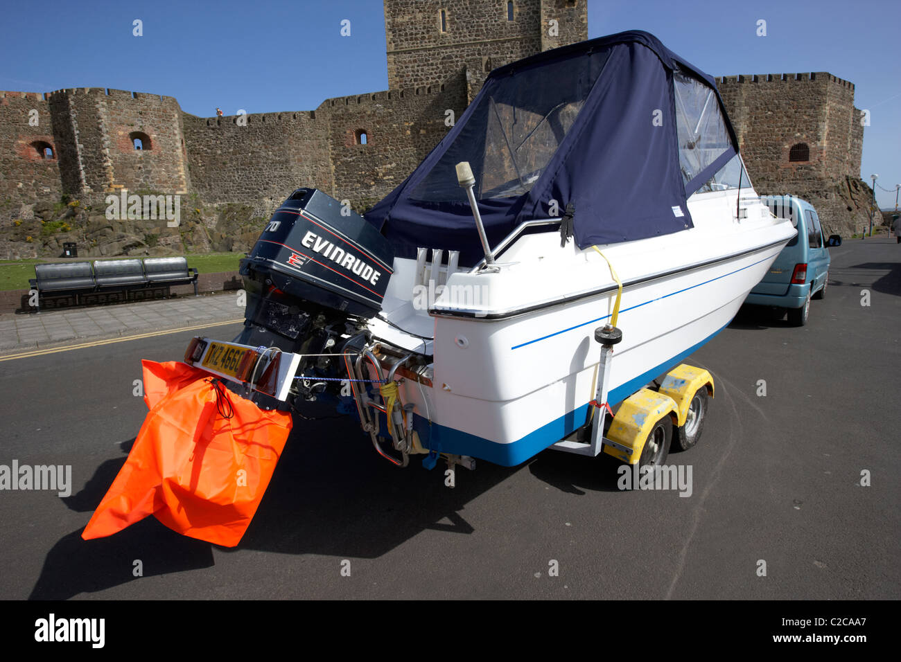outboard engines trailer light board and high visibility prop covers on a boat being towed in the uk - Stock Image