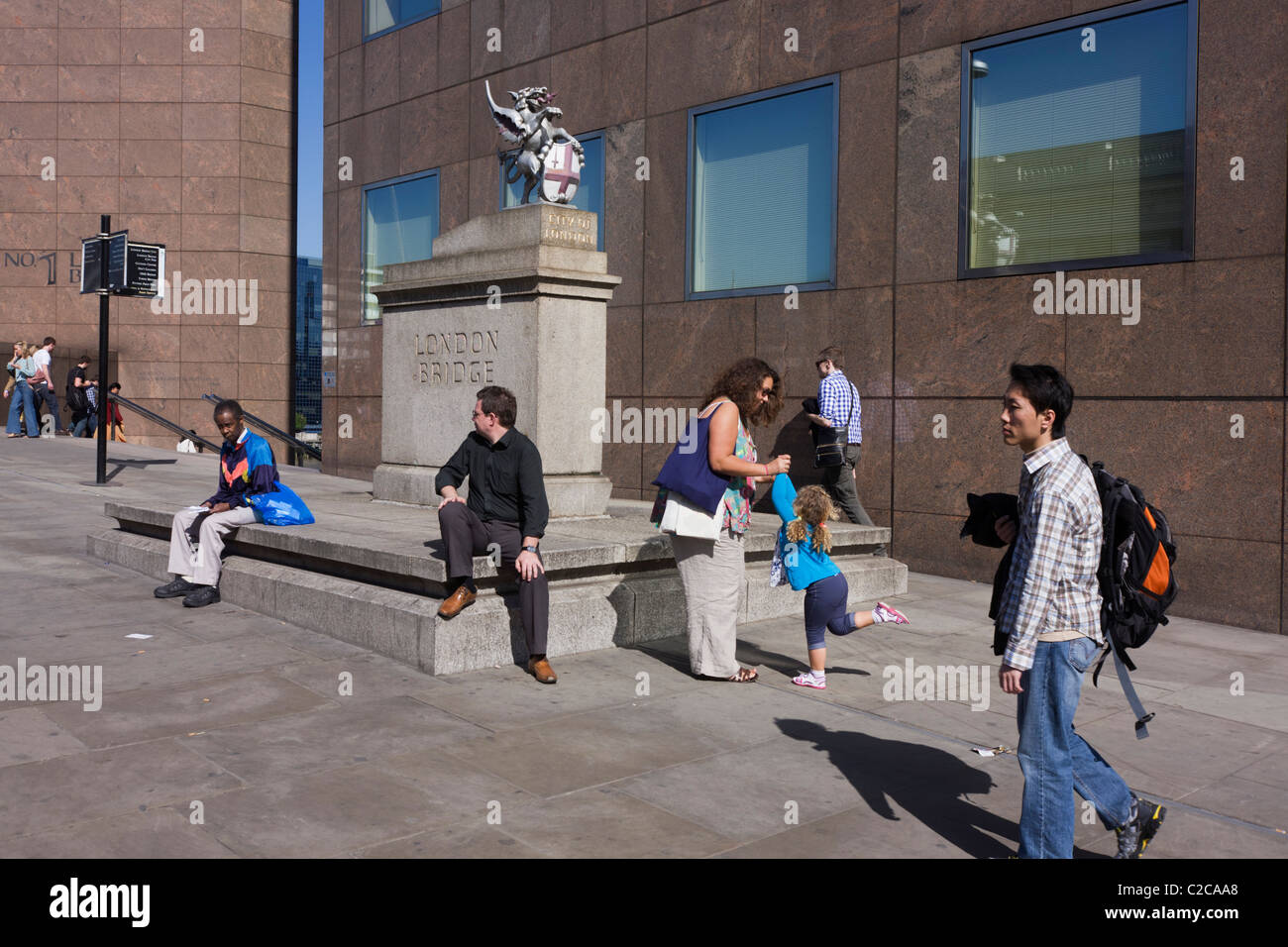 Pedestrians and passes-by at the City of London boundary griffin on London Bridge. - Stock Image
