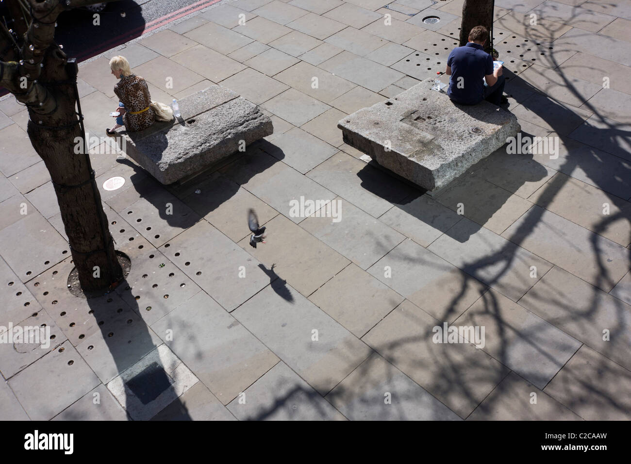 Two strangers sit adjacent each other on stone benches as a pigeon is about to land. - Stock Image