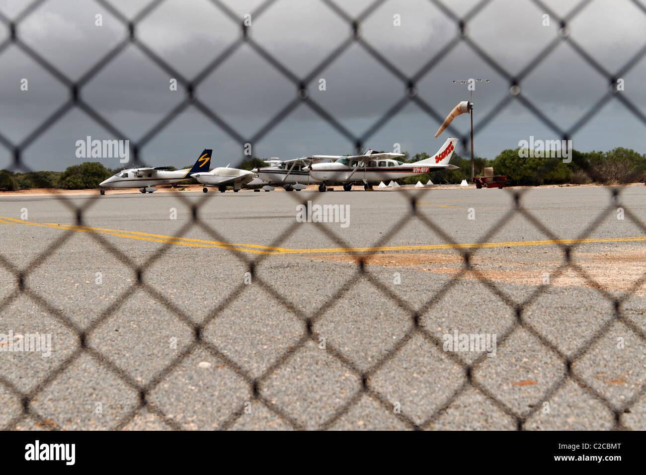 Light aircraft seen through wire fence at Denham airport, Shark Bay, Northwest Australia - Stock Image