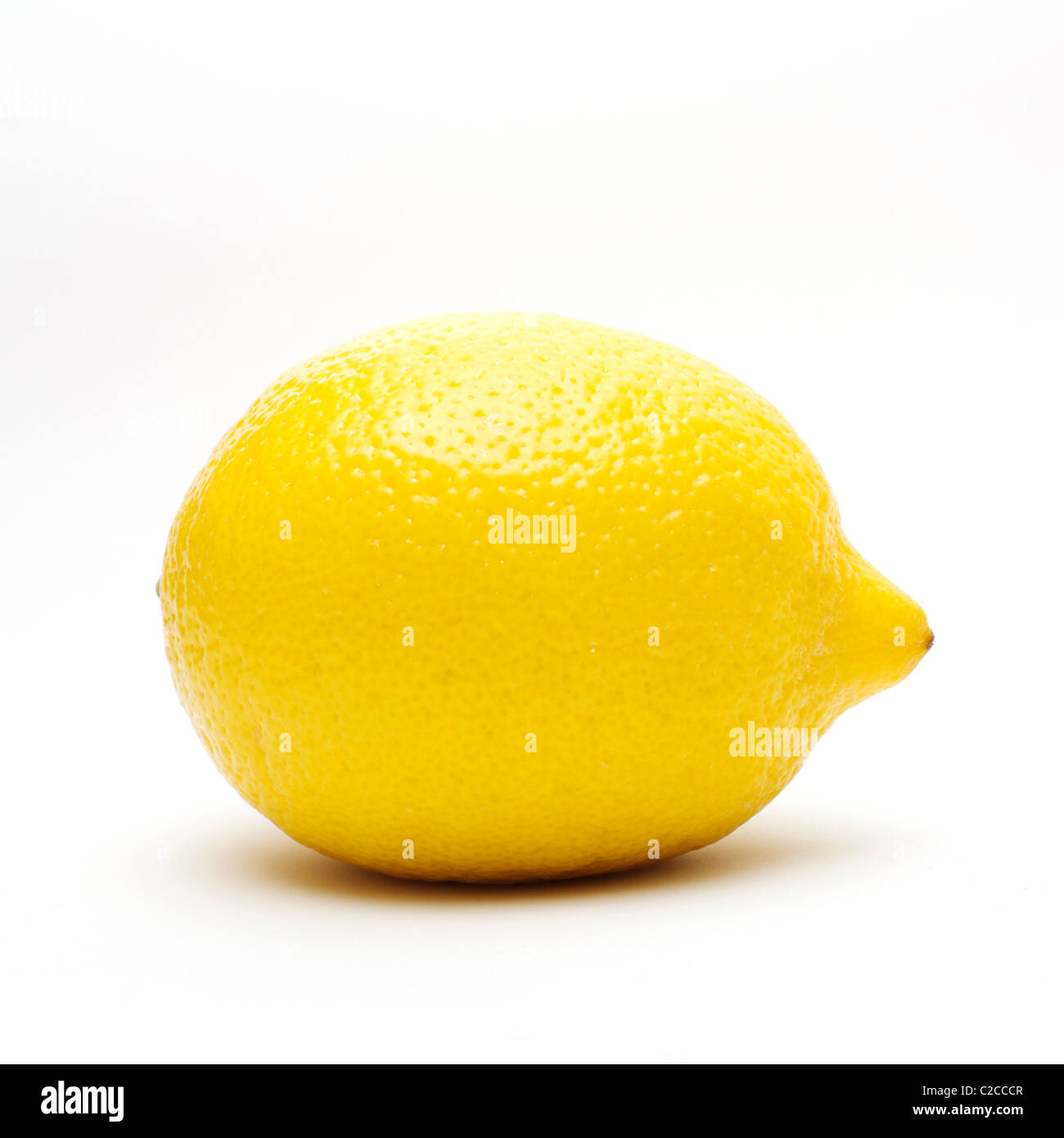 A single lemon in a high-key all white set up. - Stock Image