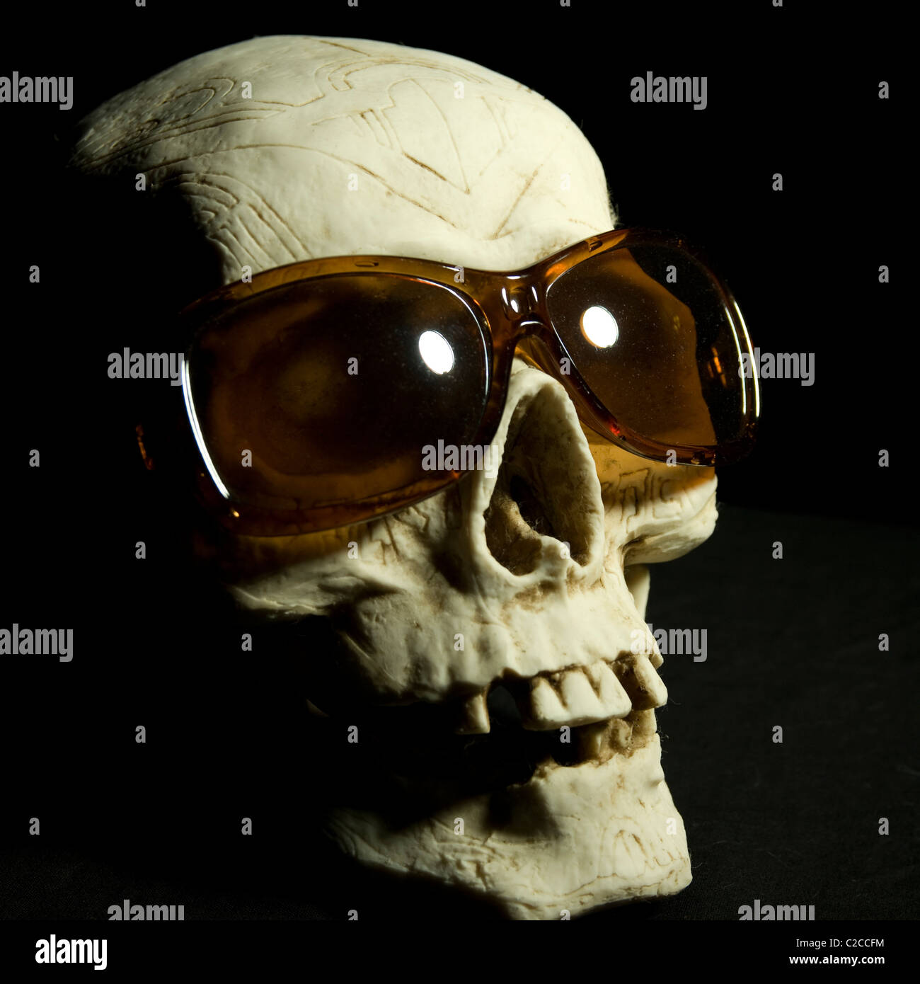 A ceramic skull wearing cheap sunglasses. - Stock Image