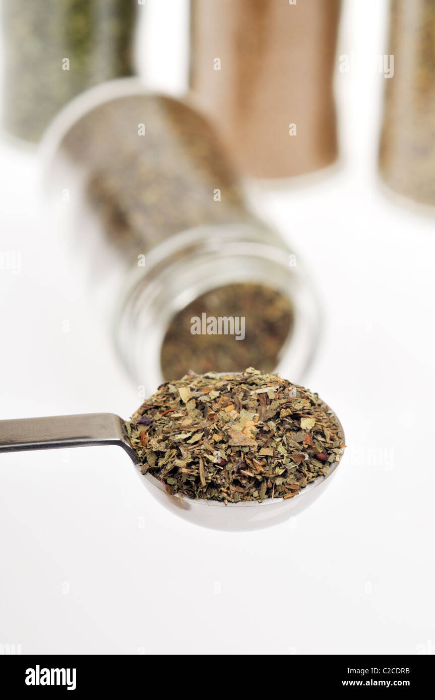 Measuring spoon filled with herb dried basil with other herb bottles in background on white. - Stock Image