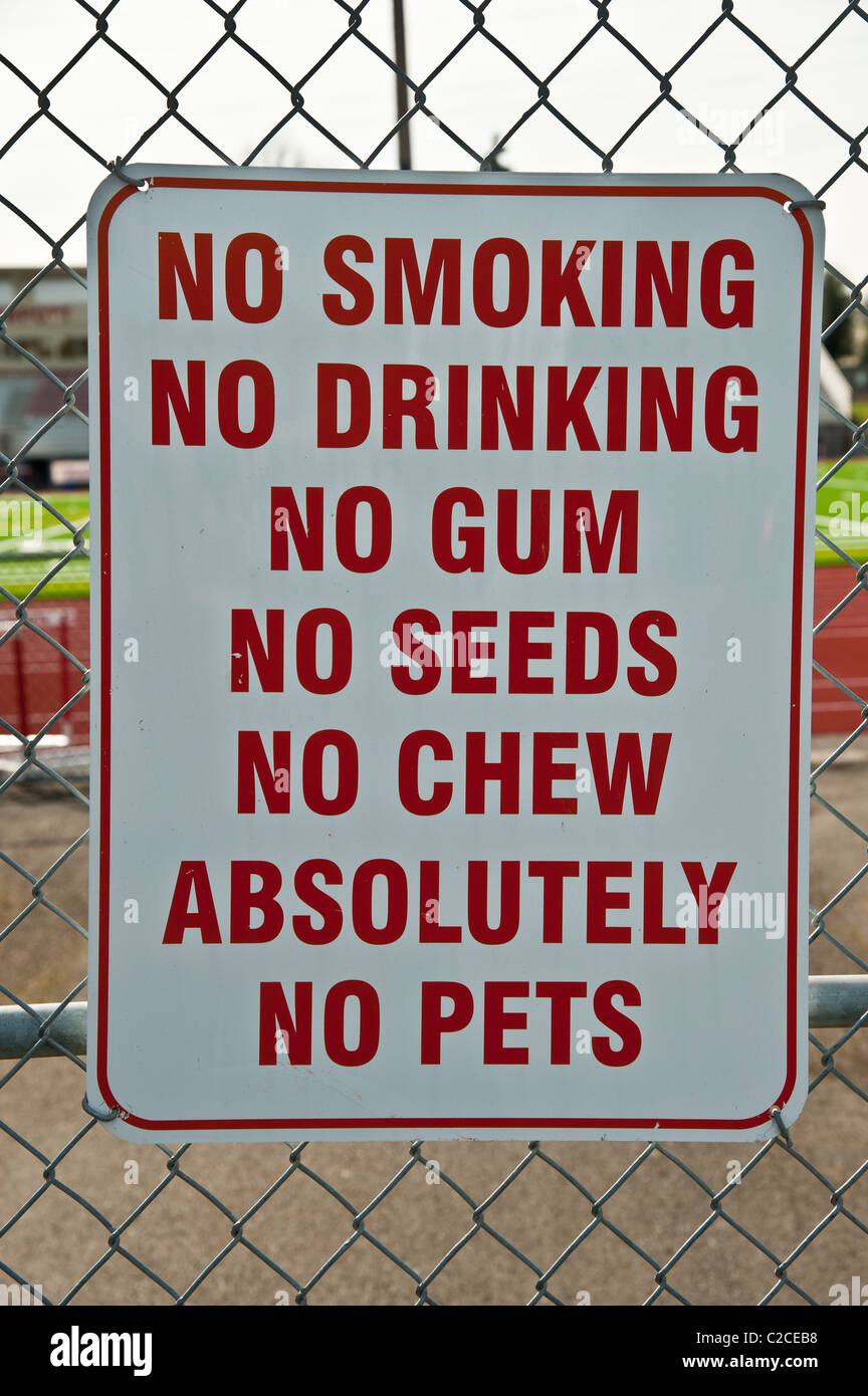 A sign in front of school yard with six No's - Stock Image