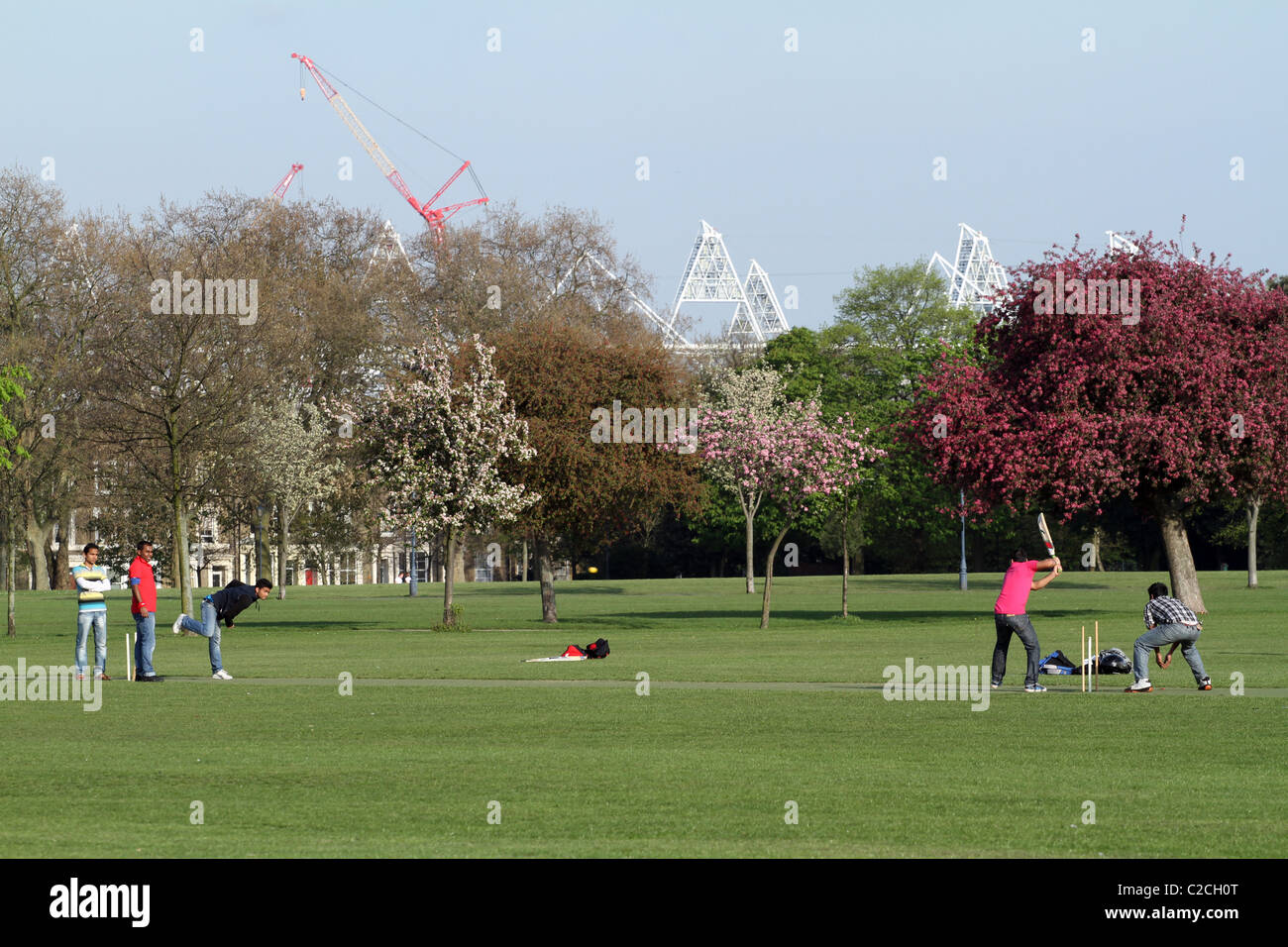 UK. CRICKET MATCH IN VICTORIA PARK WITH VIEWS OF THE LONDON 2012 OLYMPIC STADIUM Stock Photo