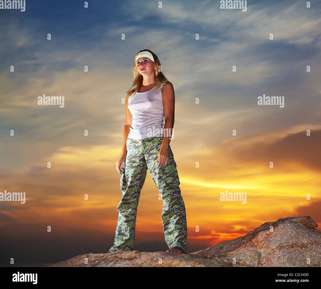 Military woman staying aon the mountain peak at sunrise time - Stock Image