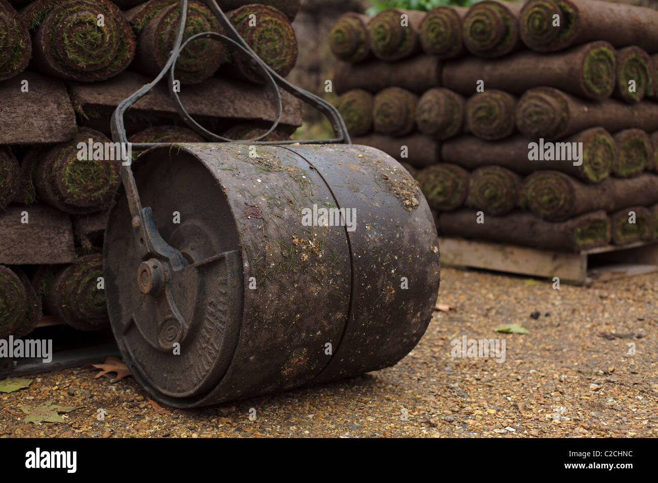 A grass roller and rolls of instant lawn on pallets. - Stock Image
