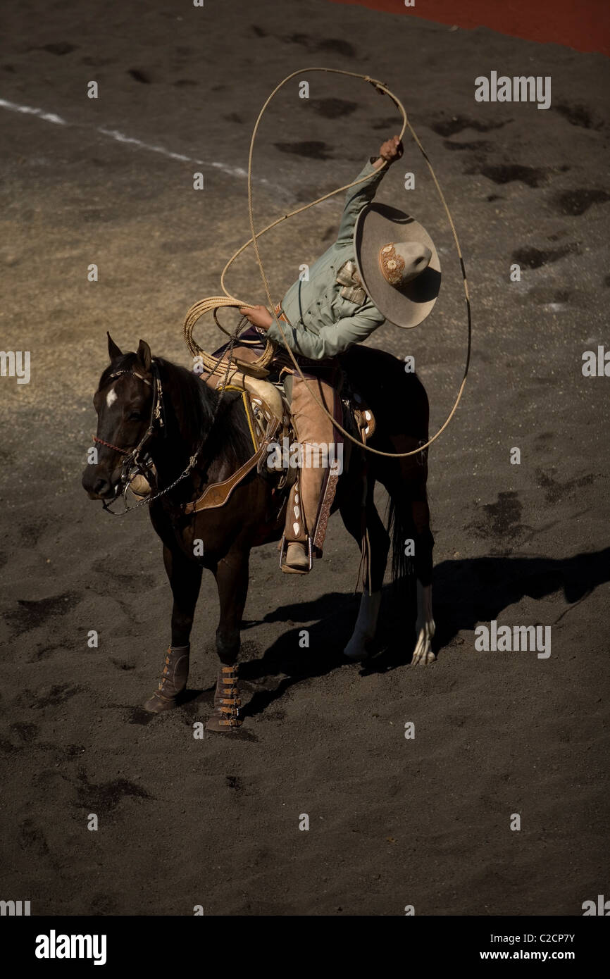 A Mexican Charro uses his lasso during a charreria exhibition in Mexico City, Mexico - Stock Image