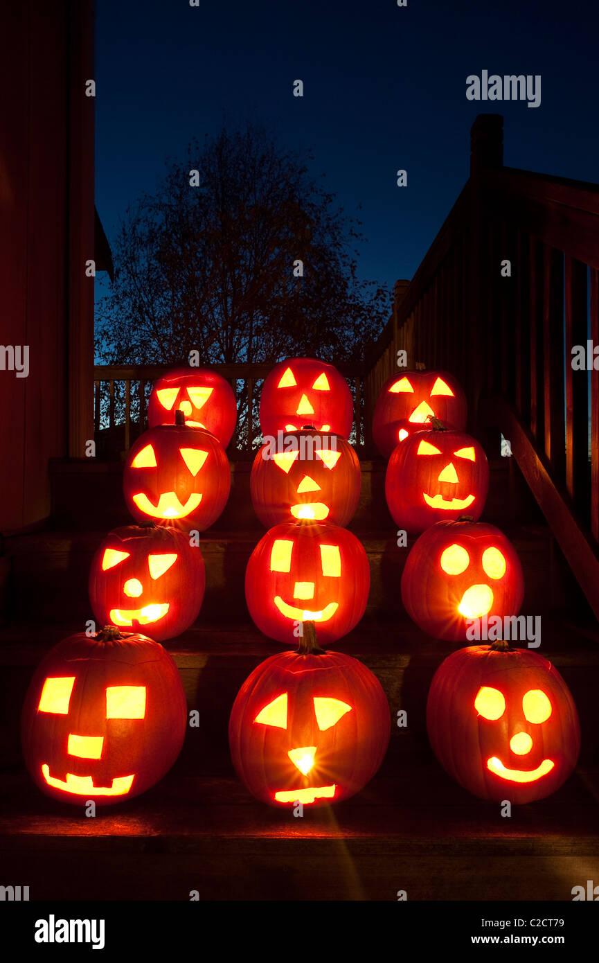 Lit Pumpkins on house steps on Halloween - Stock Image