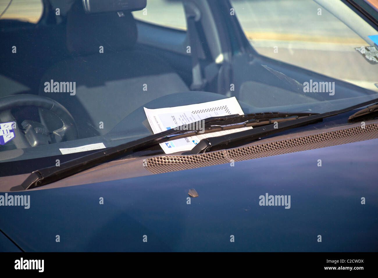 Borough of Poole penalty charge notice placed under car windscreen wipers for parking on double yellow lines - Stock Image