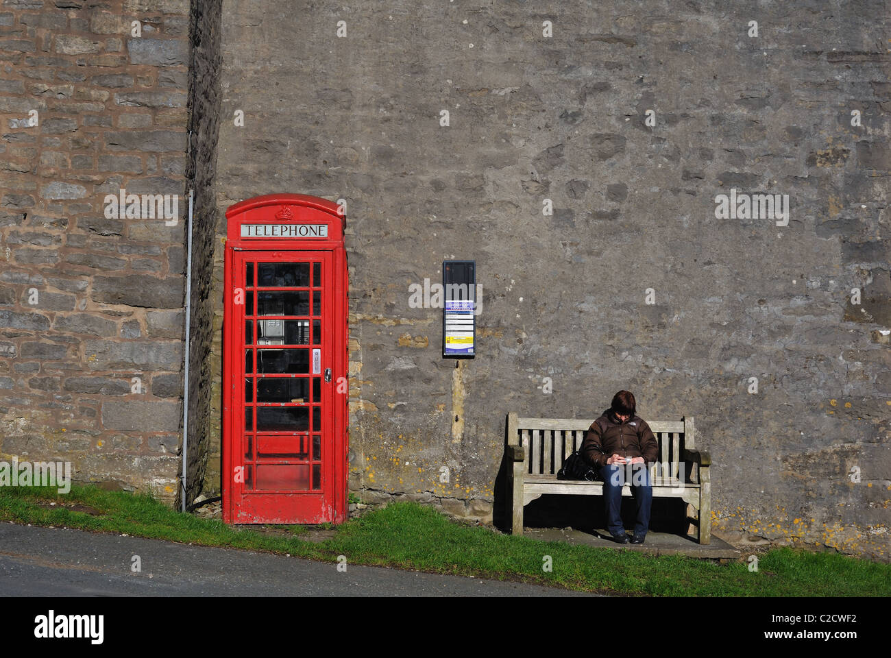 woman sat on a bench next to red telephone box texting on a mobile phone - Stock Image