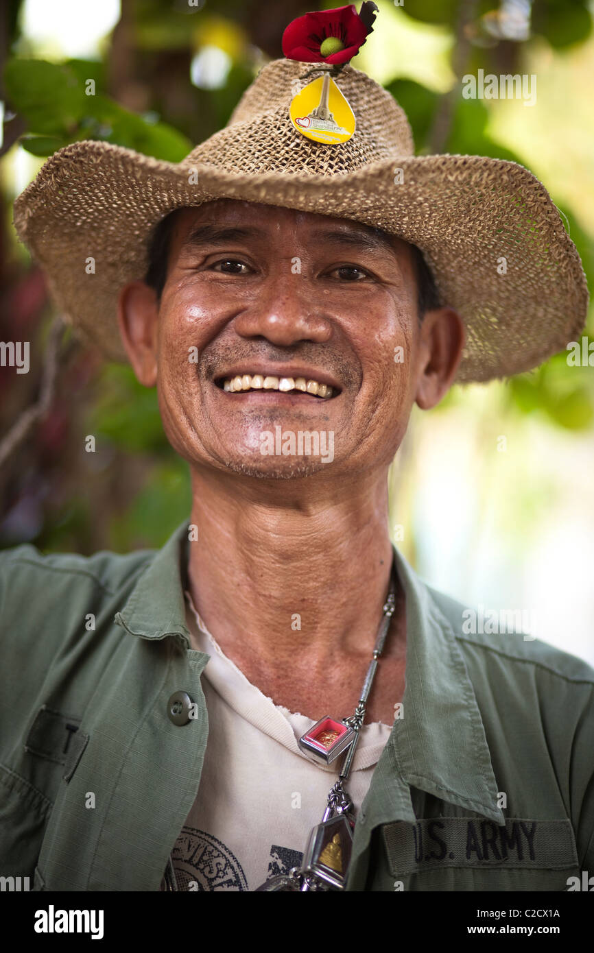 Thai ex-serviceman wearing a lot of Phra (Thai amulet) with smile. Lampang Thailand - Stock Image