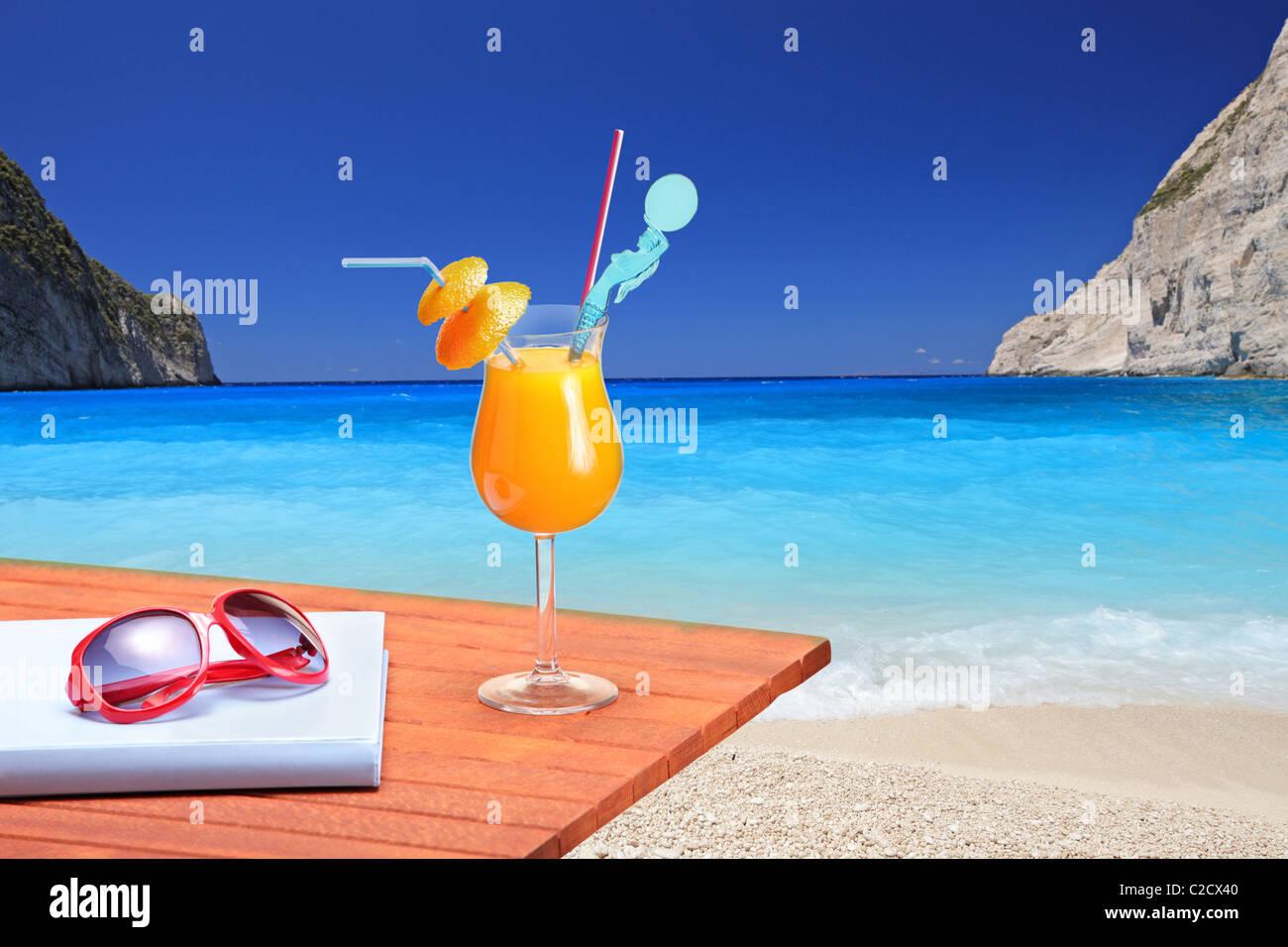 Orange cocktail on a beach table at Navagio beach on Zakynthos island - Stock Image