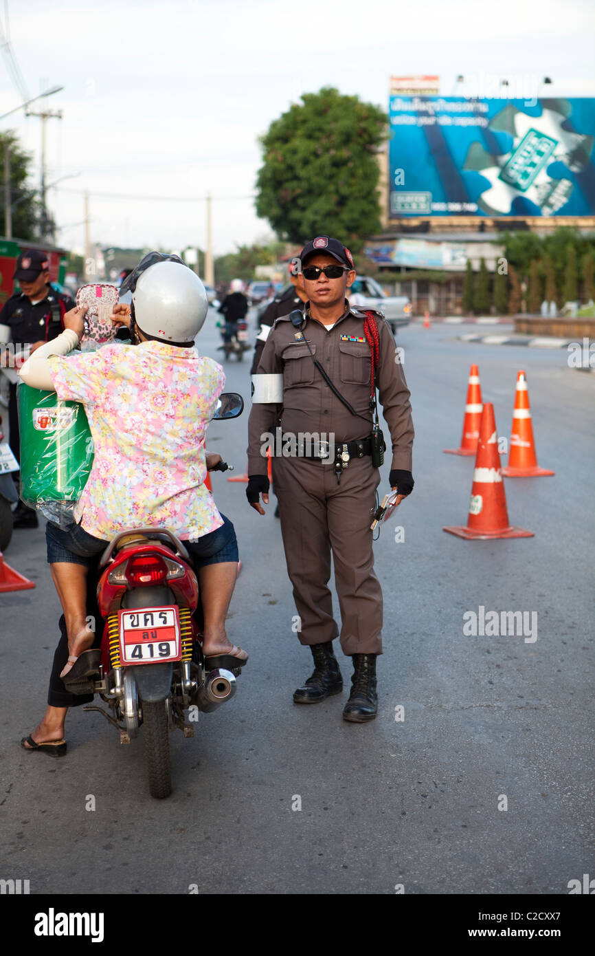 Thailand traffic police check the driving license with helmet and tax sticker on the road in Lampang city, Thailand - Stock Image