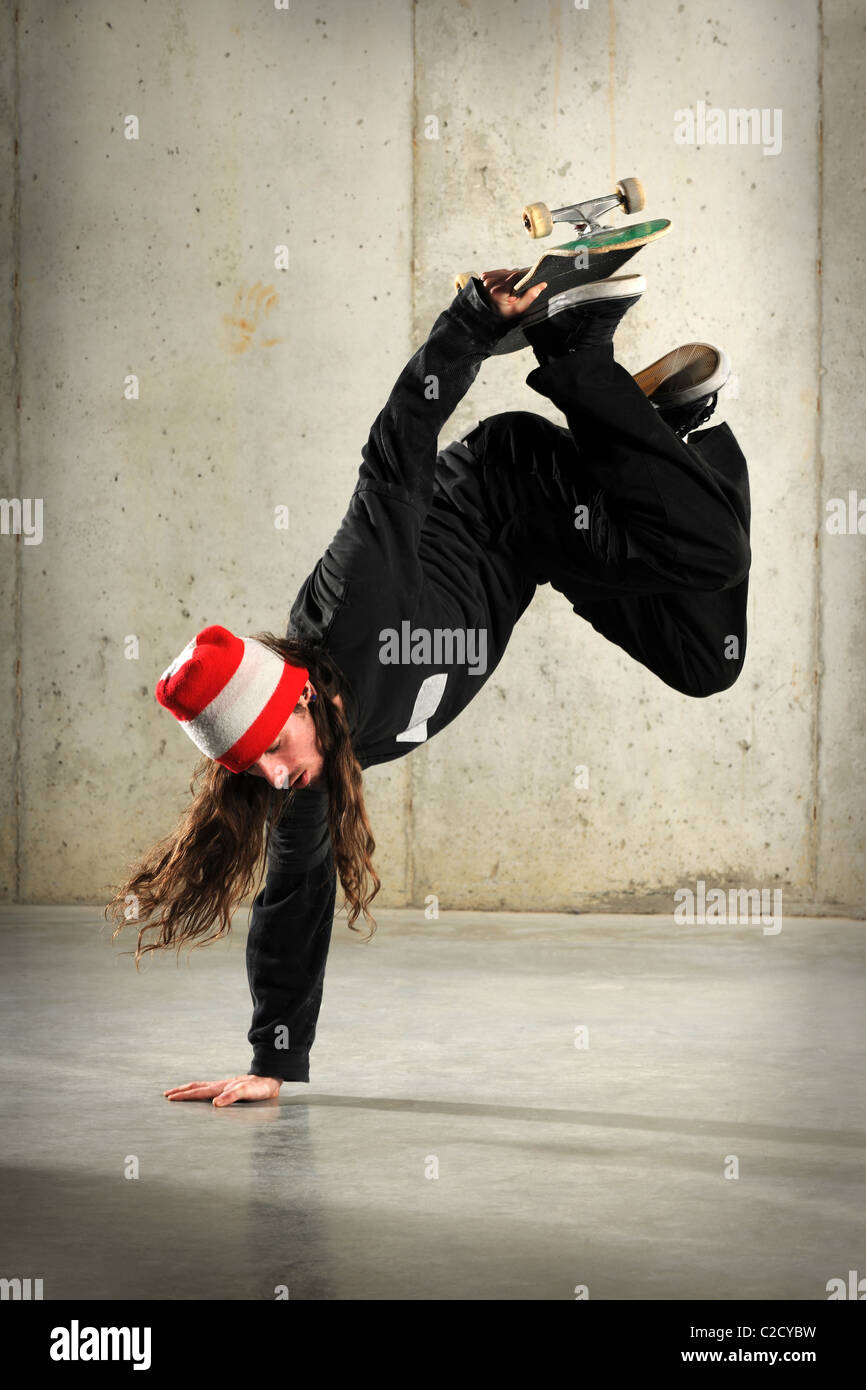 Young man with skateboard performing handstand trick - Stock Image