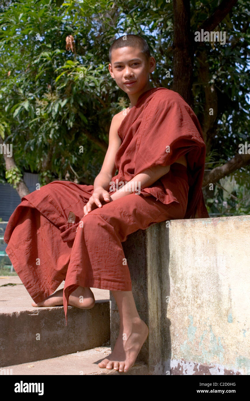 A young Buddhist monk is relaxing at a beautiful temple in Tachilek, Burma (Myanmar). Stock Photo