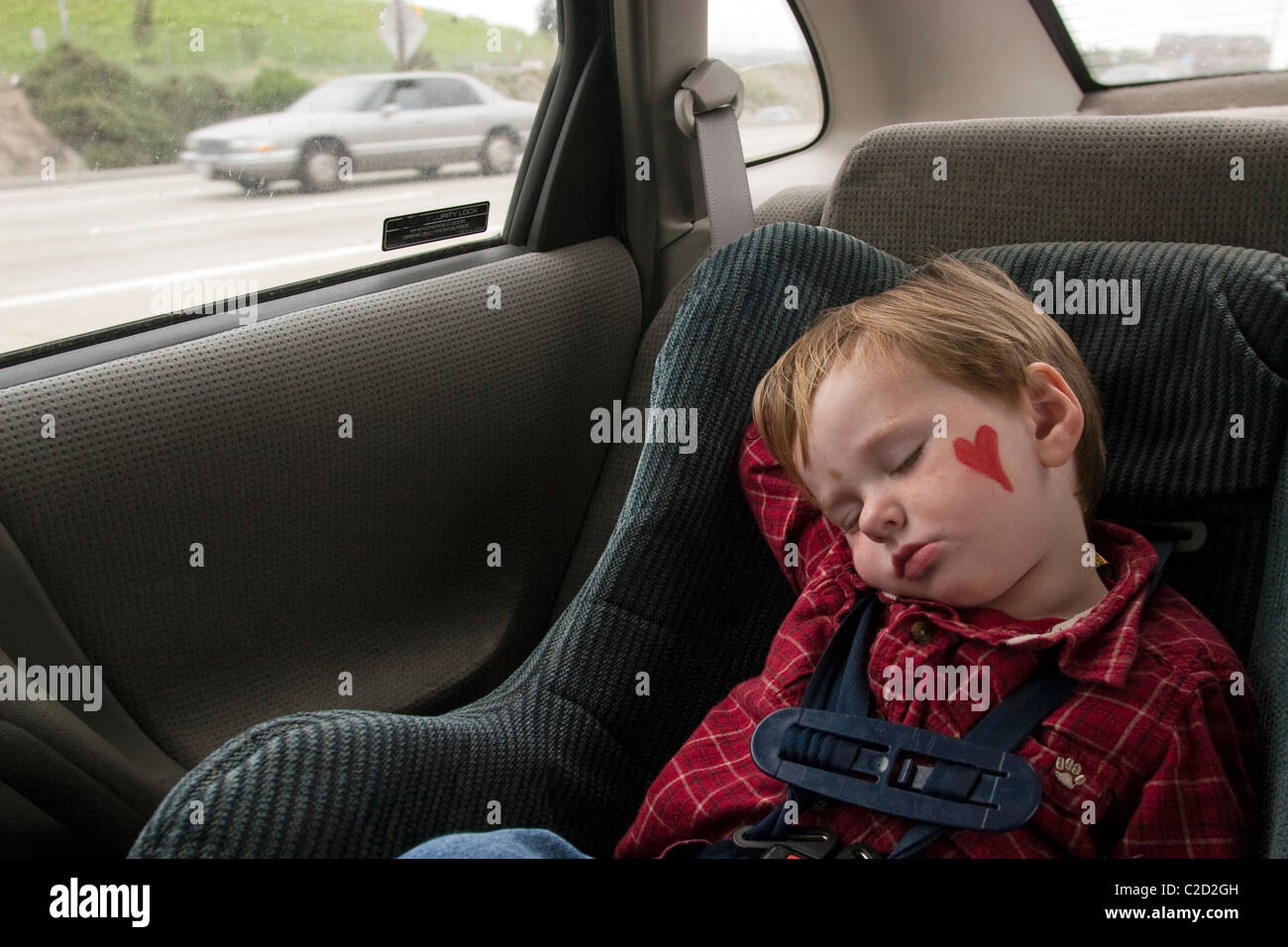 A 3 Year Old Boy Napping In His Car Seat After Family Outing