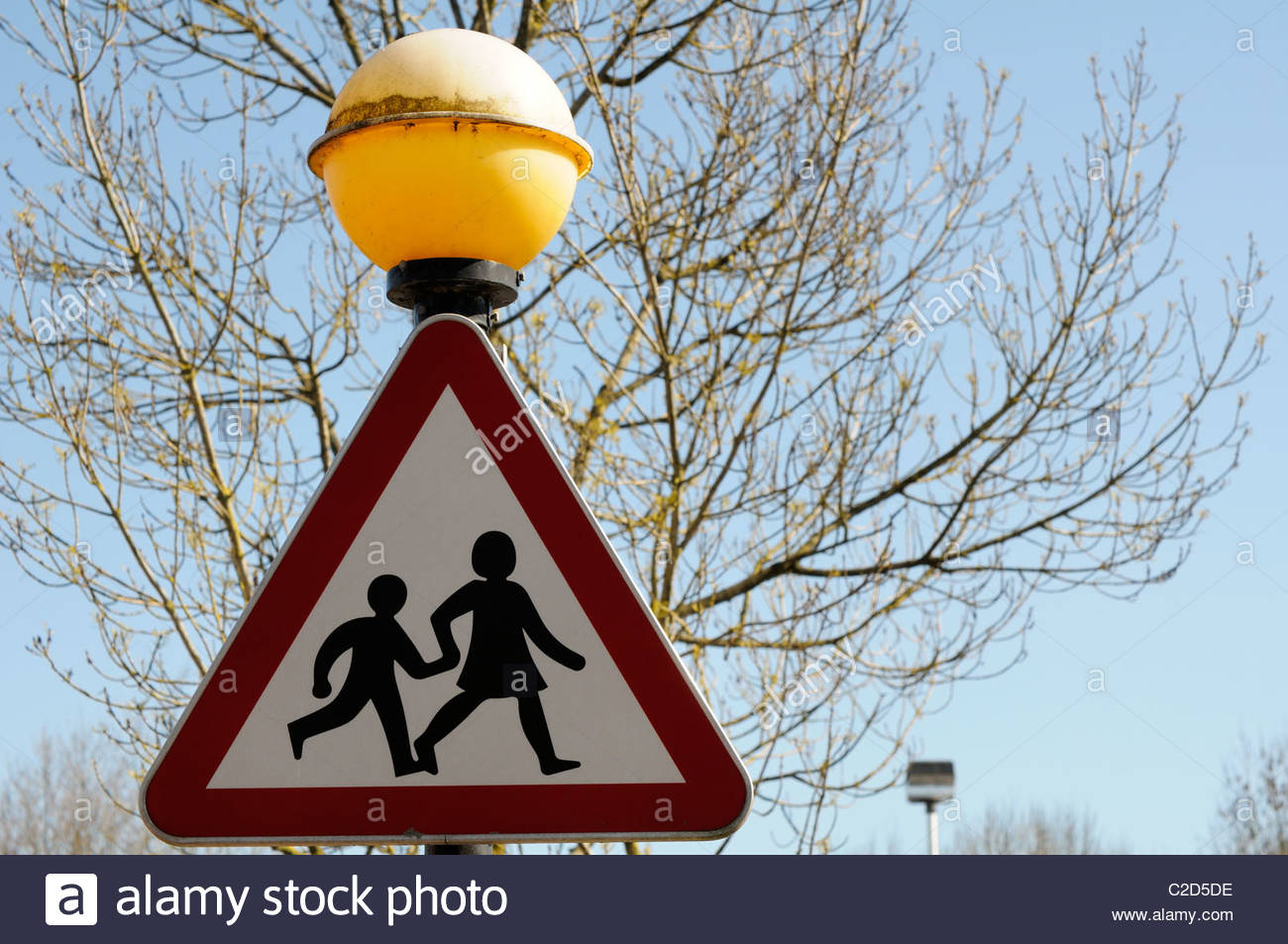 Looking up at a school children crossing road sign below a belisha beacon at Blandford Forum in Dorset, England - Stock Image