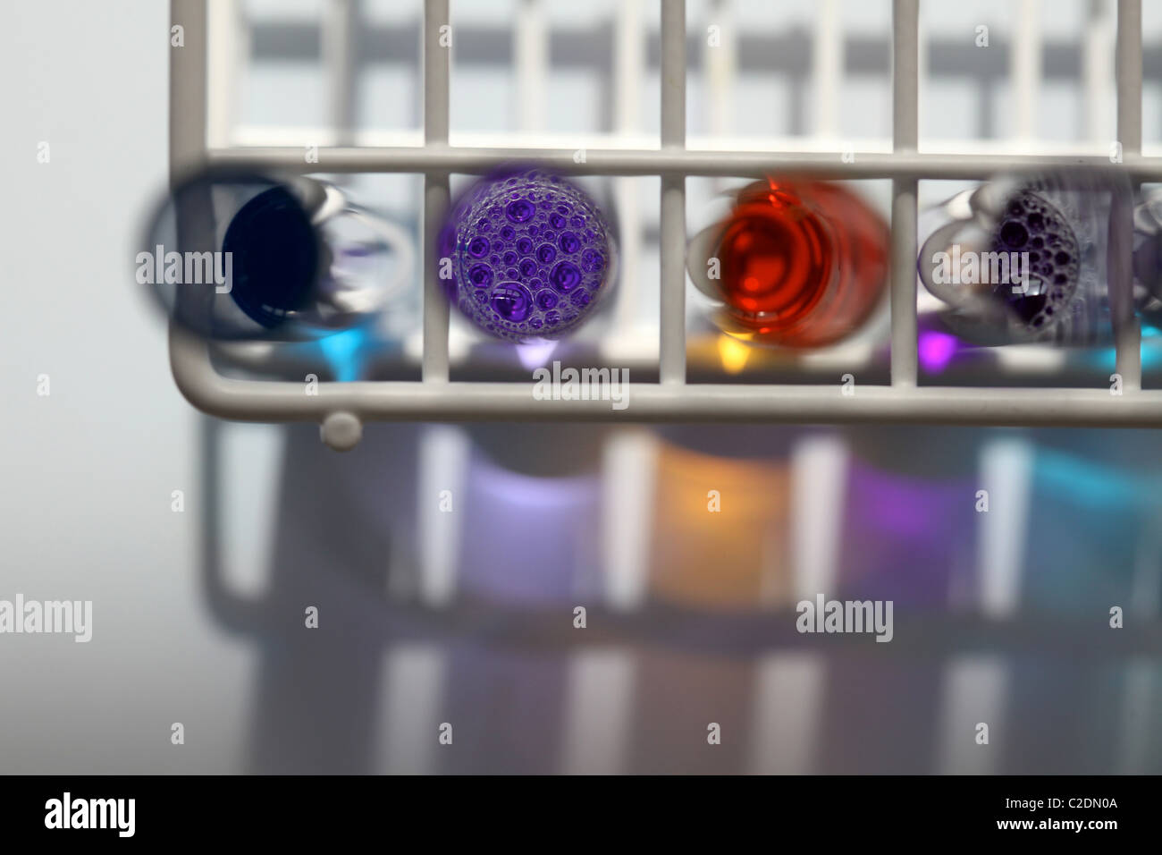 Ariel view of rack of four test tubes in a laboratory containing liquids in various colours - Stock Image