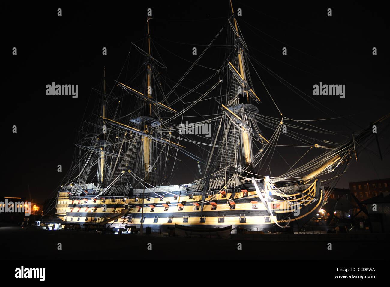 The old warship, man of war sailing ship HMS Victory, floodlit at night. - Stock Image