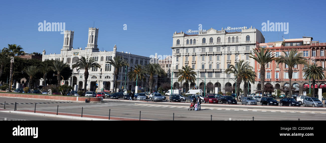 Family crossing the road in front of historical buildings by the road Via Roma, a main road by the port, in Cagliari, - Stock Image