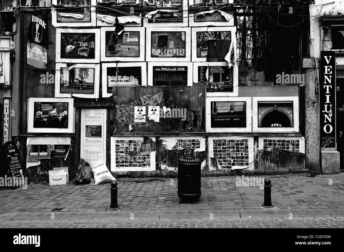 A decrepit building on Rue du Marché aux Herbes, Bruxelles/Grasmarkt, Brussels, Belgium, covered in posters Stock Photo