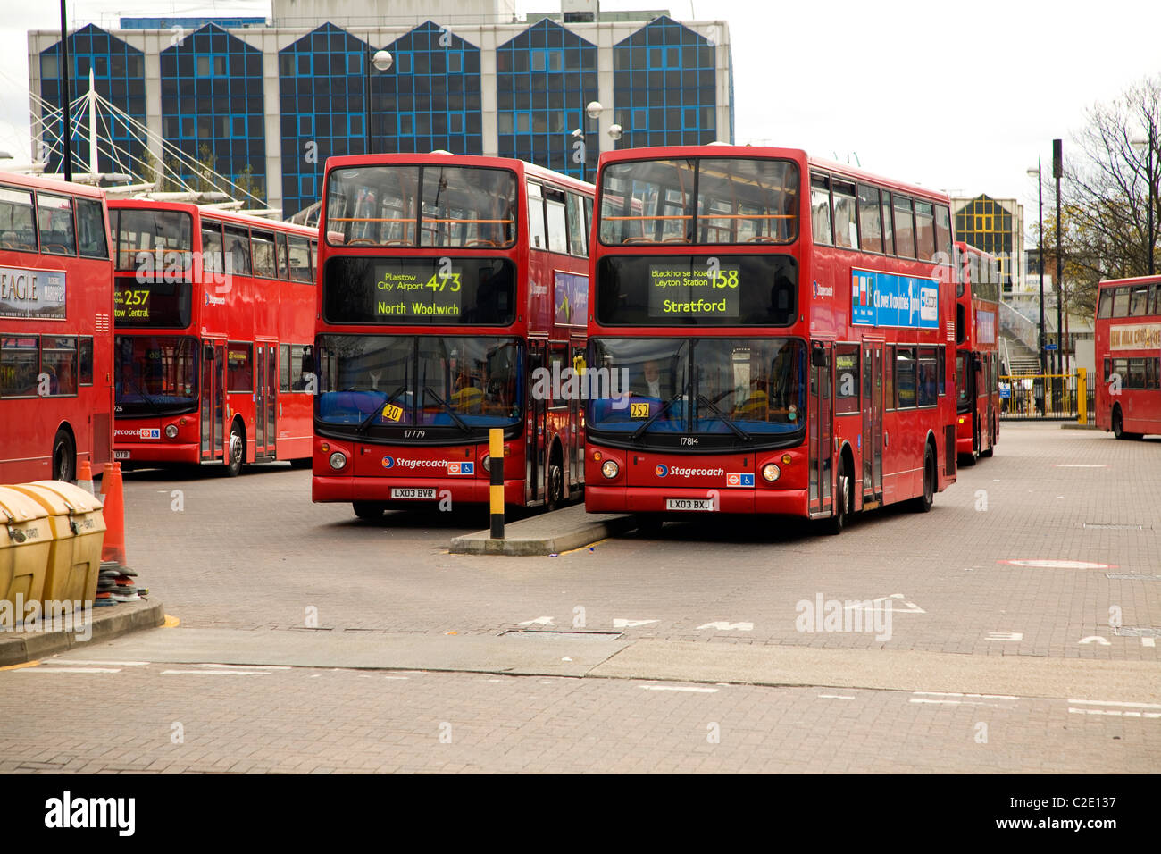 Red double decker buses terminus bus station Newham London - Stock Image