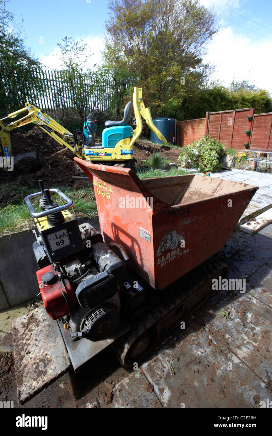 hired hi-tip dumper and micro digger excavating small garden in the uk - Stock Image