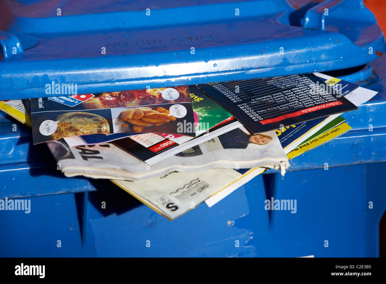 blue paper recycling bin with junk mail and local newspapers sticking out of it and lid not closed in the uk - Stock Image