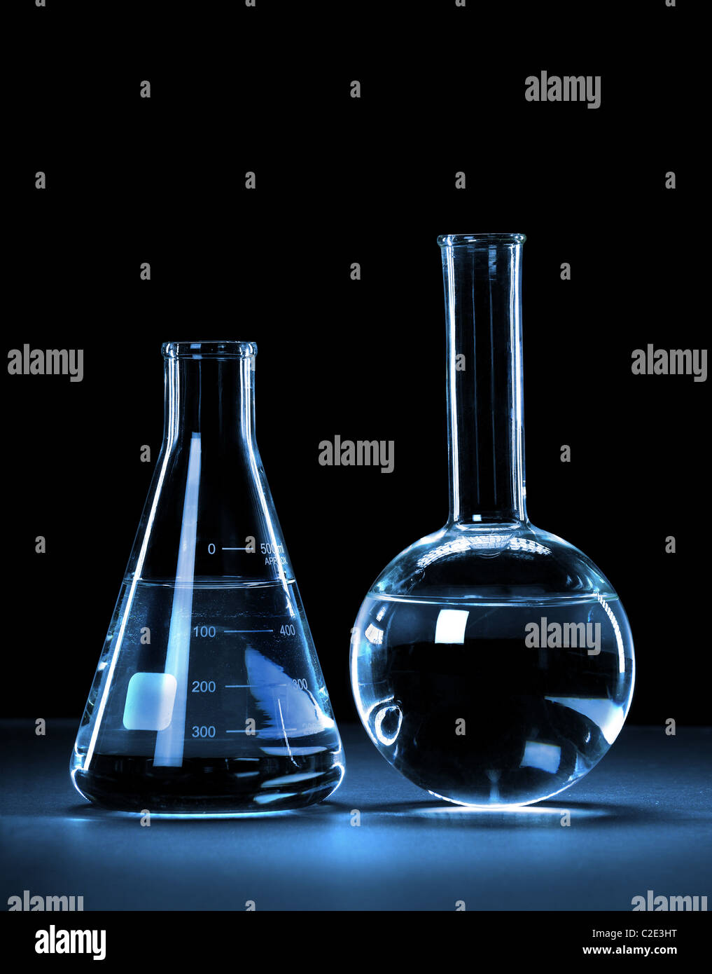 Laboratory glassware with blue light over dark background - With Clipping Path - Stock Image