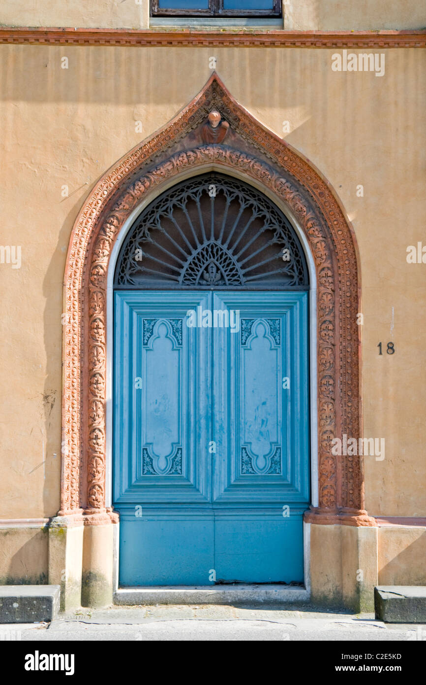 Very ornate blue painted door with a gothic style arch surround in a ...