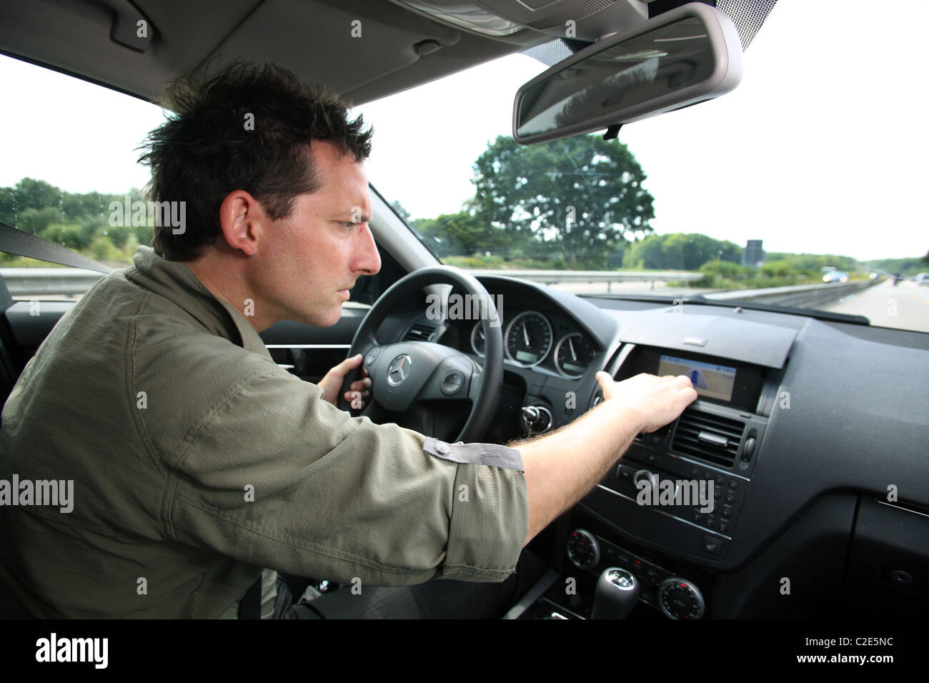 A man looking at his car navigation system while driving - Stock Image