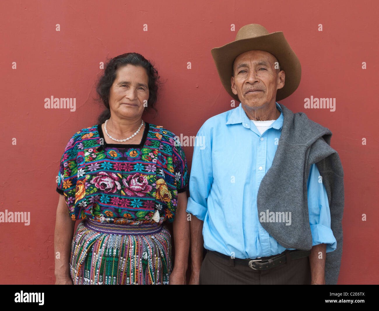 An older Guatemalan married couple stand in front of a deep terra cotta colored wall in traditional dress looking - Stock Image