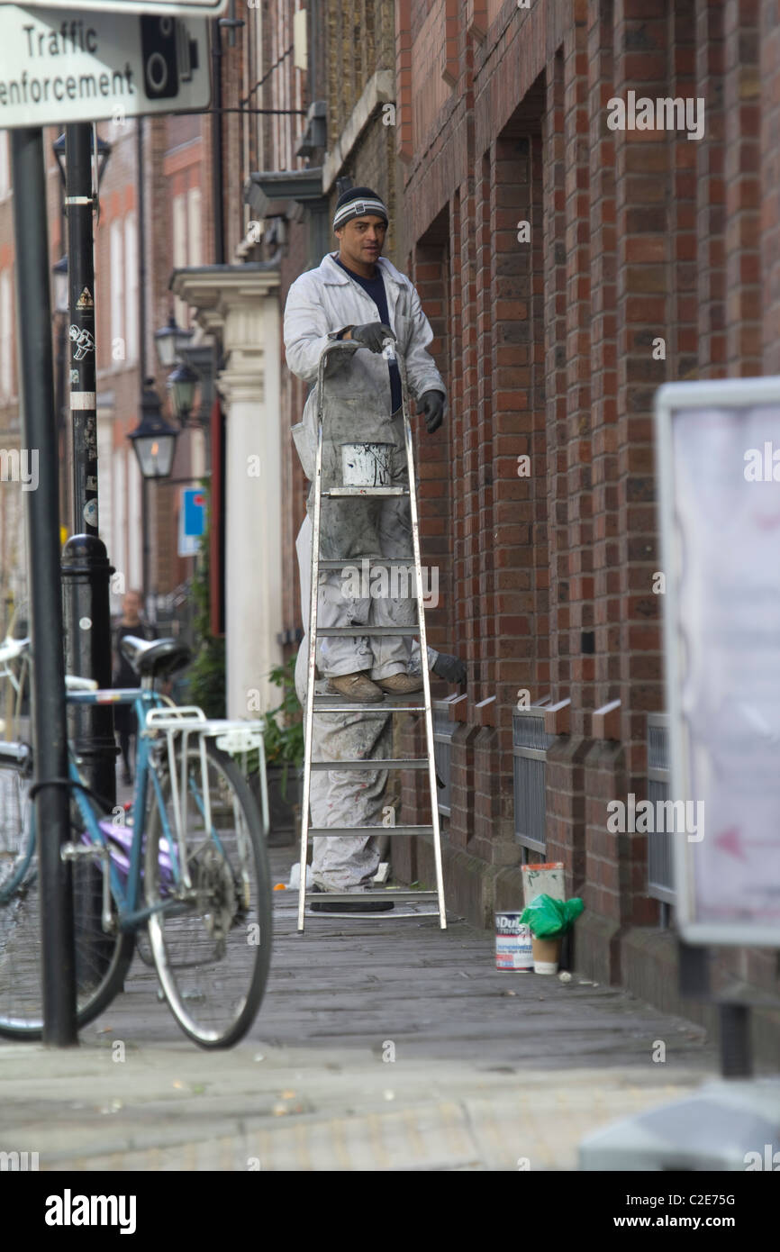 Painter decorator, on stepladder painting exterior of building in Central London Stock Photo
