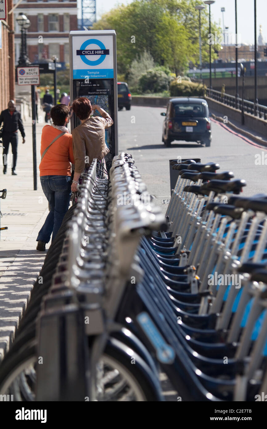 line of boris barclays hire bikes with two tourists checking routes - Stock Image