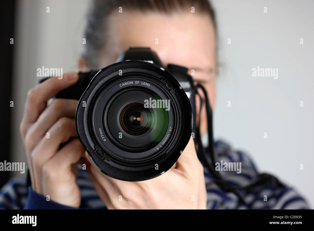 Person, female, looks through the viewfinder of a digital single lens reflex camera. - Stock Image