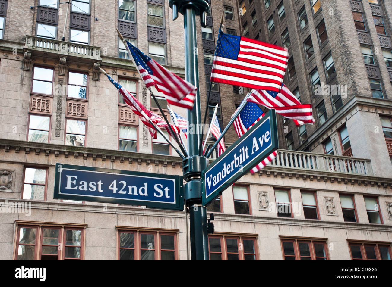 East 42nd Street and Vanderbilt Avenue street sign with American flags, Manhattan, New York City, USA - Stock Image