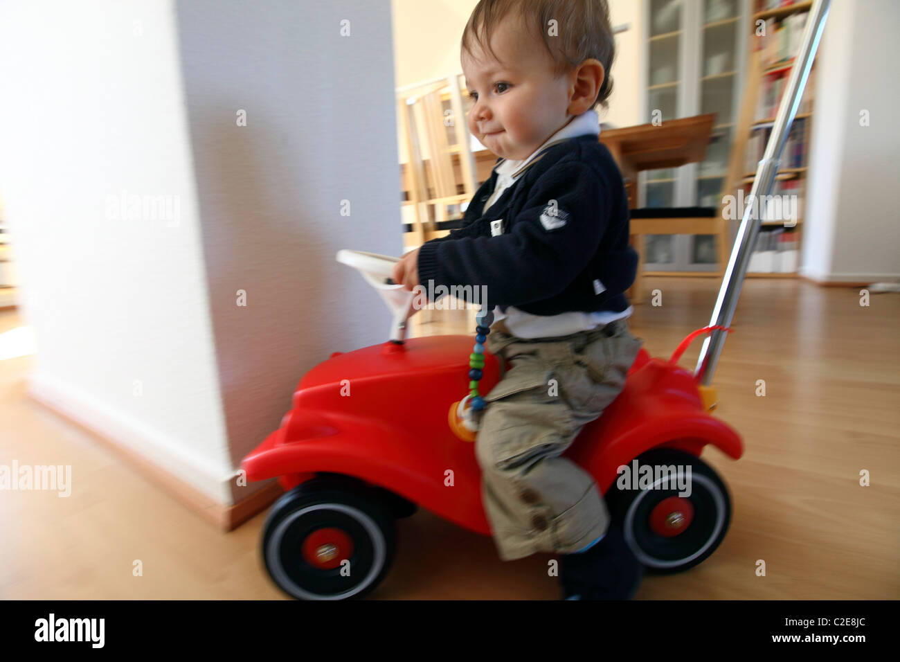 little boy baby 10 month old playing with a bobby car. Black Bedroom Furniture Sets. Home Design Ideas