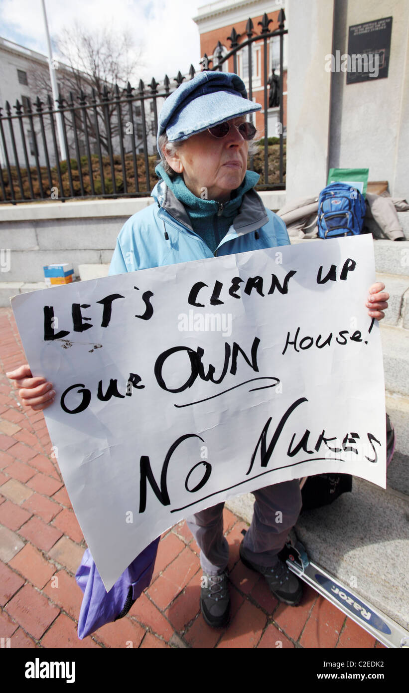 A woman holds a sign during an anti nuclear rally in front of the State House in Boston Massachusetts - Stock Image