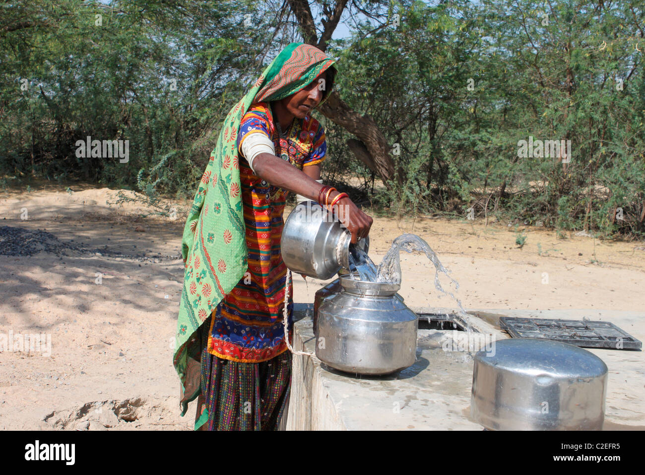 A rural woman collecting water from a well - Stock Image