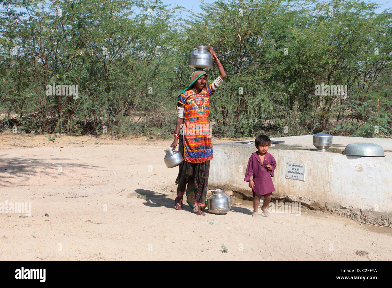 A woman carrying water - Stock Image