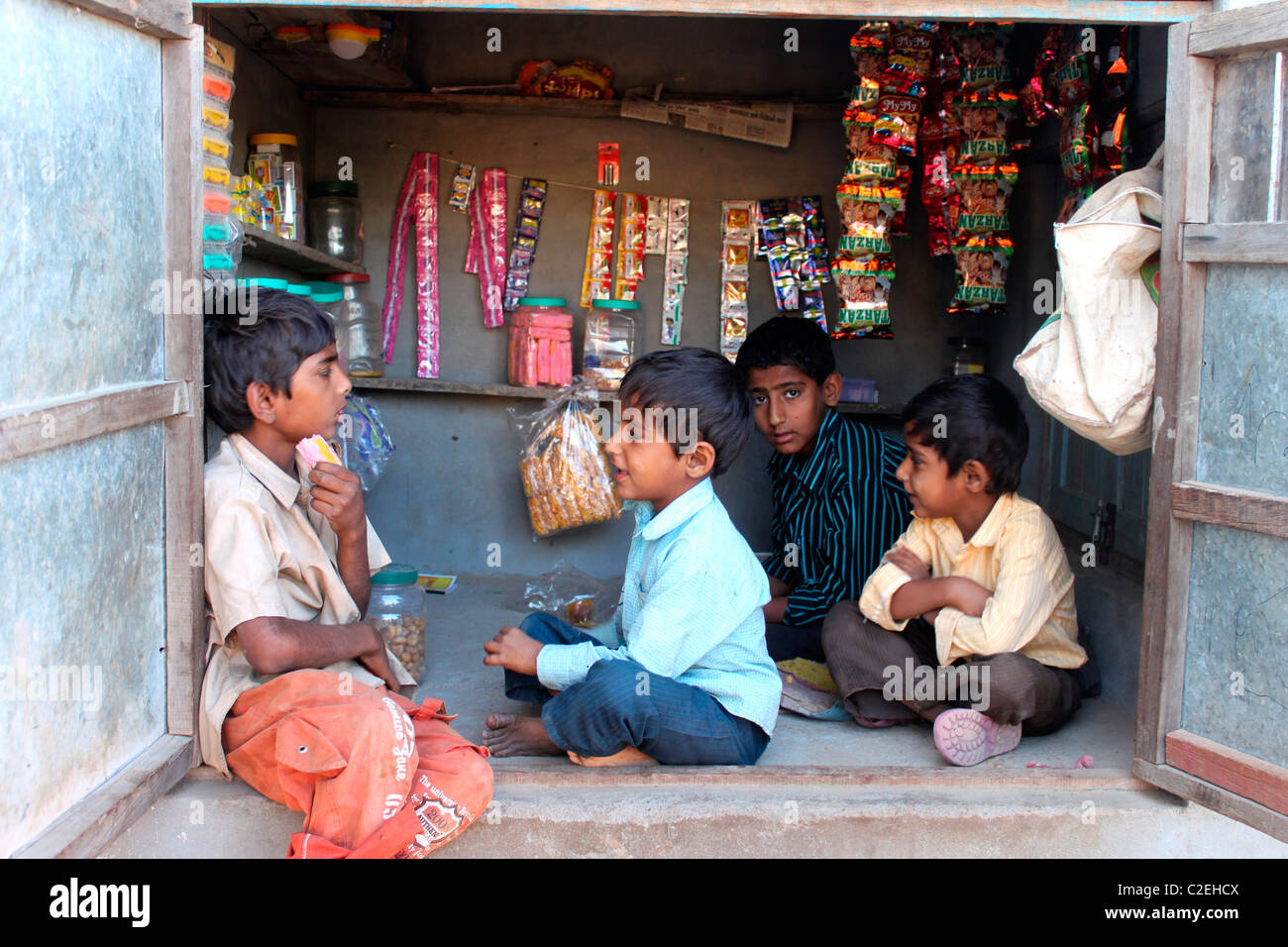 Rural children talking in a stationary shop in Rural Gujarat, India - Stock Image