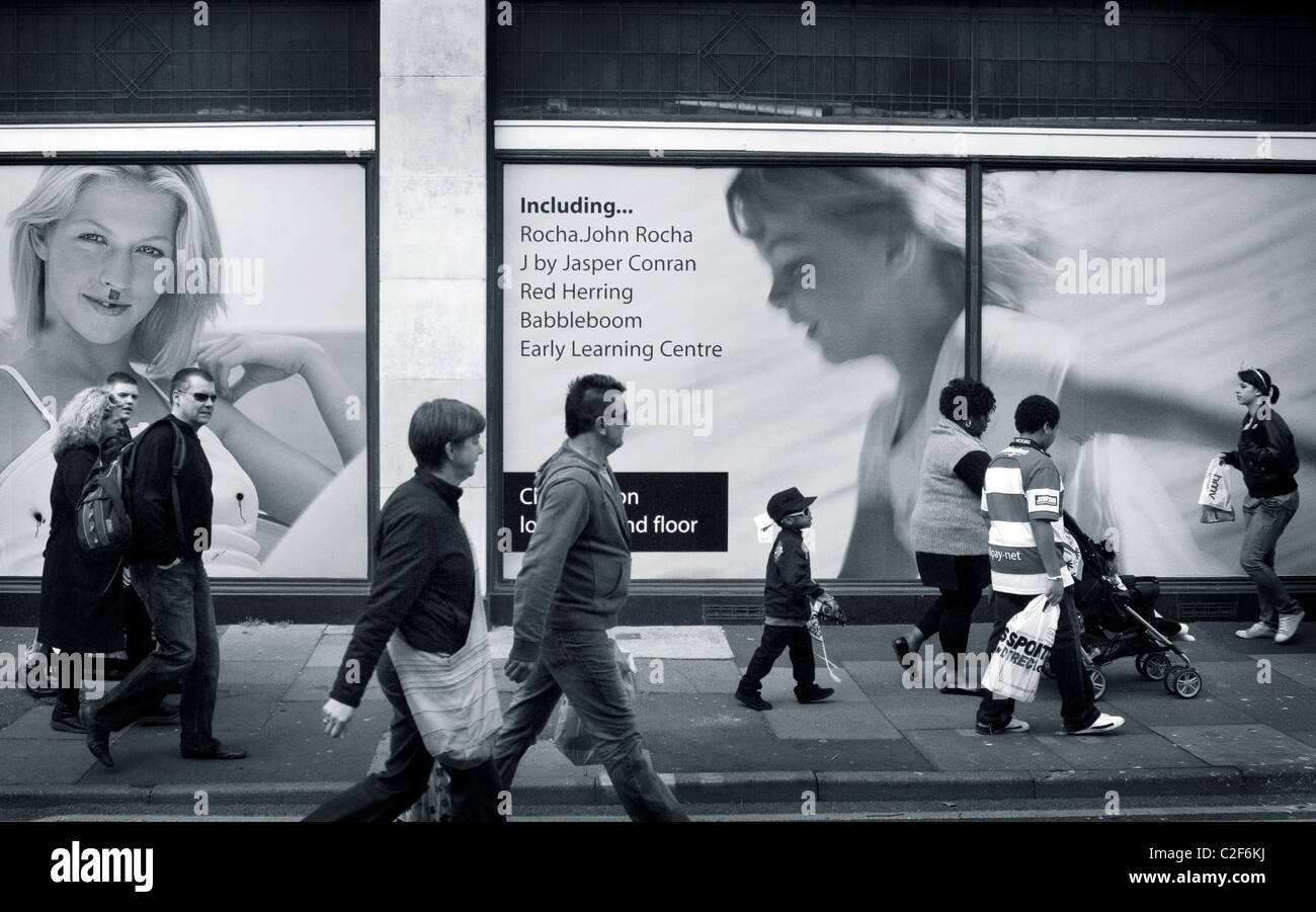 British / UK shopping street with advertising posters / billboards behind busy shoppers. - Stock Image